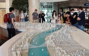 Professor James Hevia points out a feature of a 3D scale model of Shanghai during an excursion for students during the East Asian Civilizations study abroad program.
