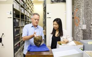 professor examines mask with student